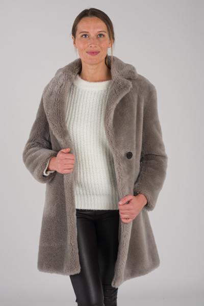 Mantel aus echter gestrickter Schafwolle.              title=